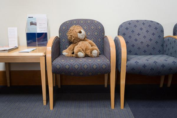 A plush toy sitting in the waiting room of a family doctor's office.