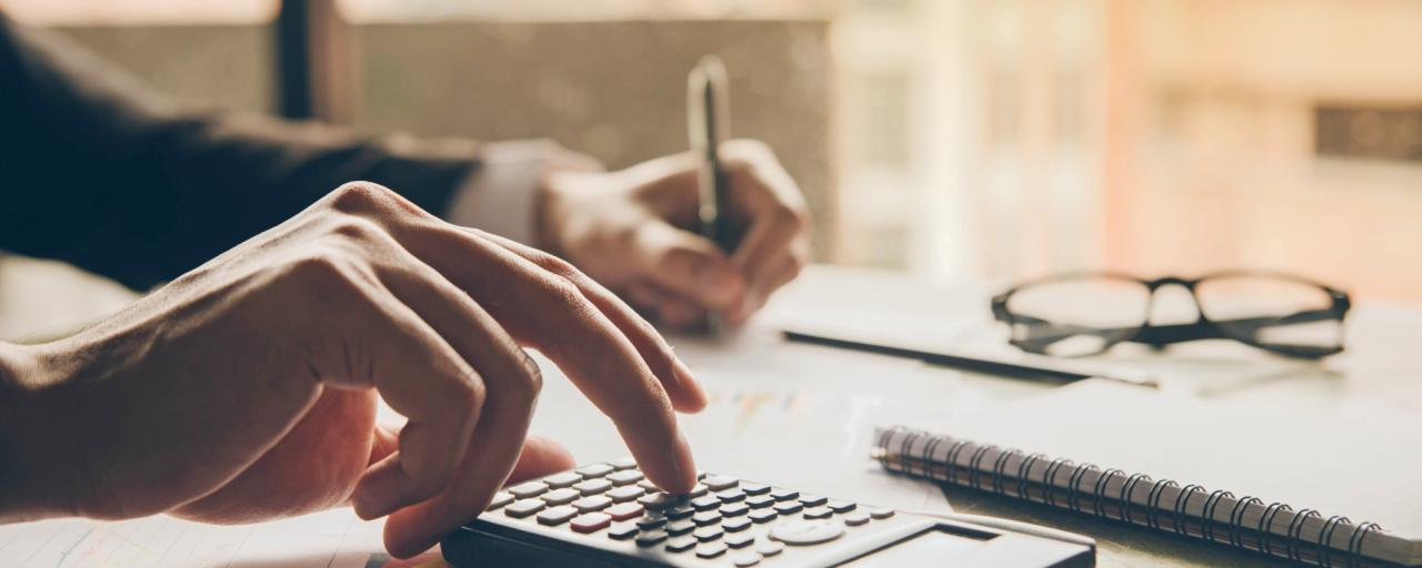 Close up hands of a lawyer doing finances with using calculator and writing note in office