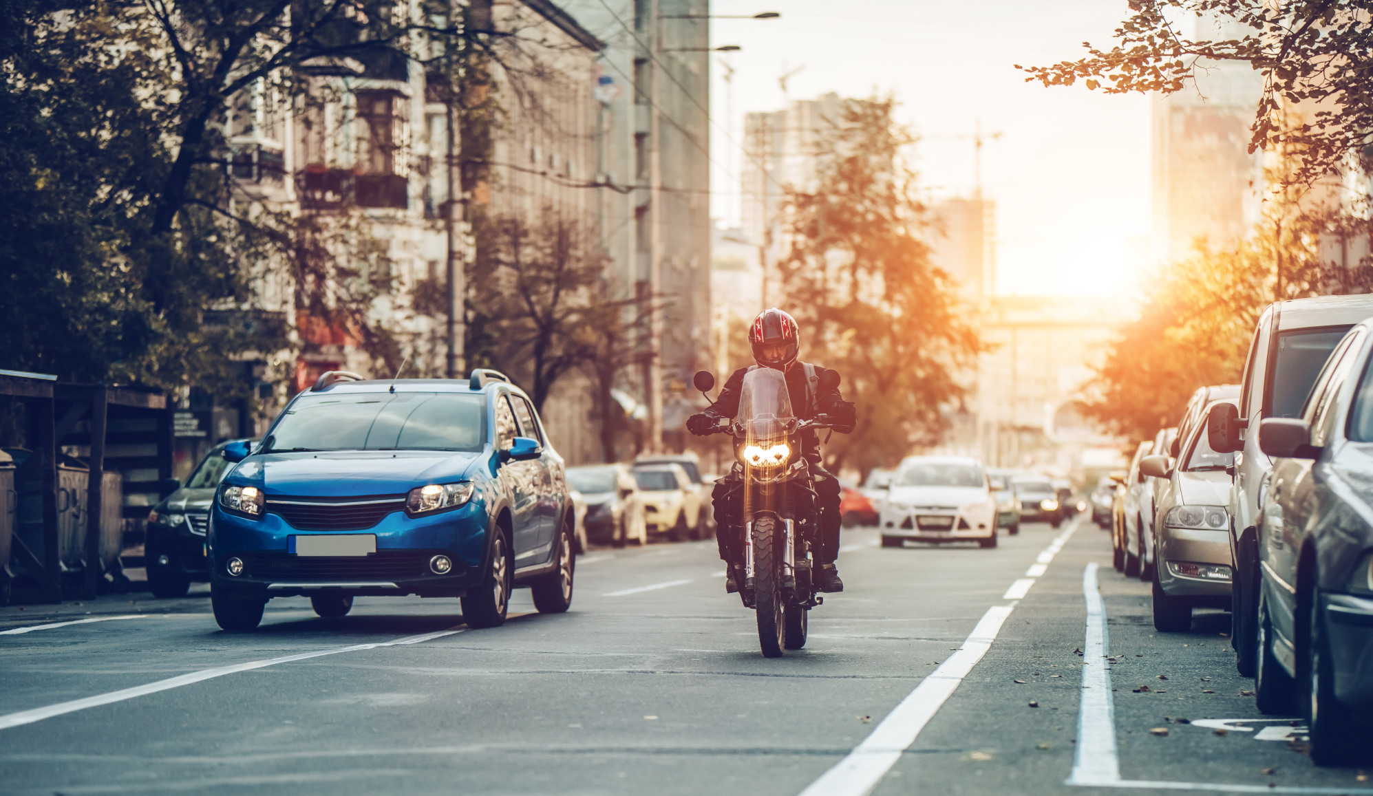 Motorcycle riding down street with parked cars on riders left and moving vehicle on rider's right